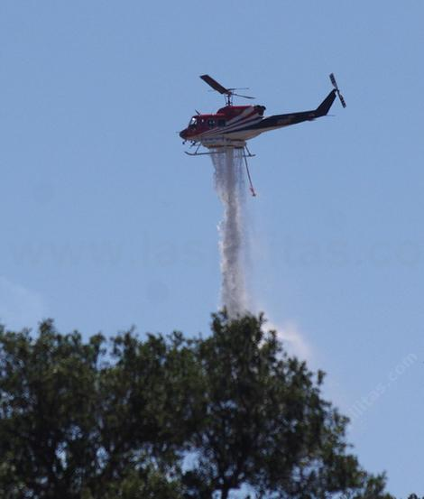 A helicopter dropping water across the street from the nursery. - grid24_12