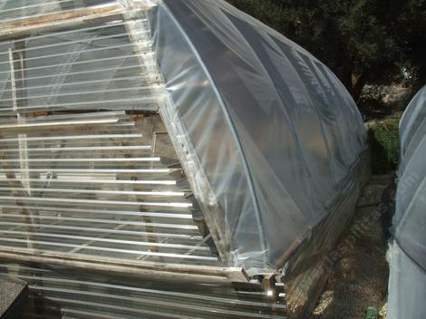 Greenhouse sides can be of pvc, polycarbonate, fiberglass or poly. We've found the best was polycarbonate for the first couple of feet.  The rest of the greenhouse can be poly. Notice the polycarbonate vent. Greenhouses have to be vented. - grid24_12