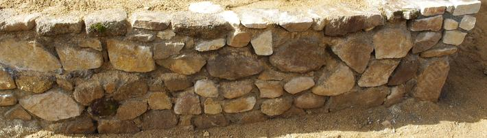 This rock-wall was used to cover a concrete foundation.  Not enough wire was used behind it and the mortar was not 3 sand to one plastic cement, but the wall turned out rather well.